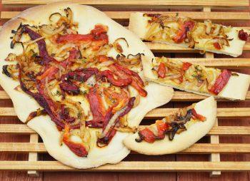 Plat brood met ui en geroosterde paprika